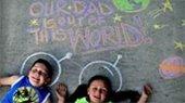 Two children playing with sidewalk chalk