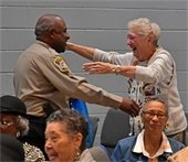 Senior Citizen hugging a Deputy from the Sheriff's
