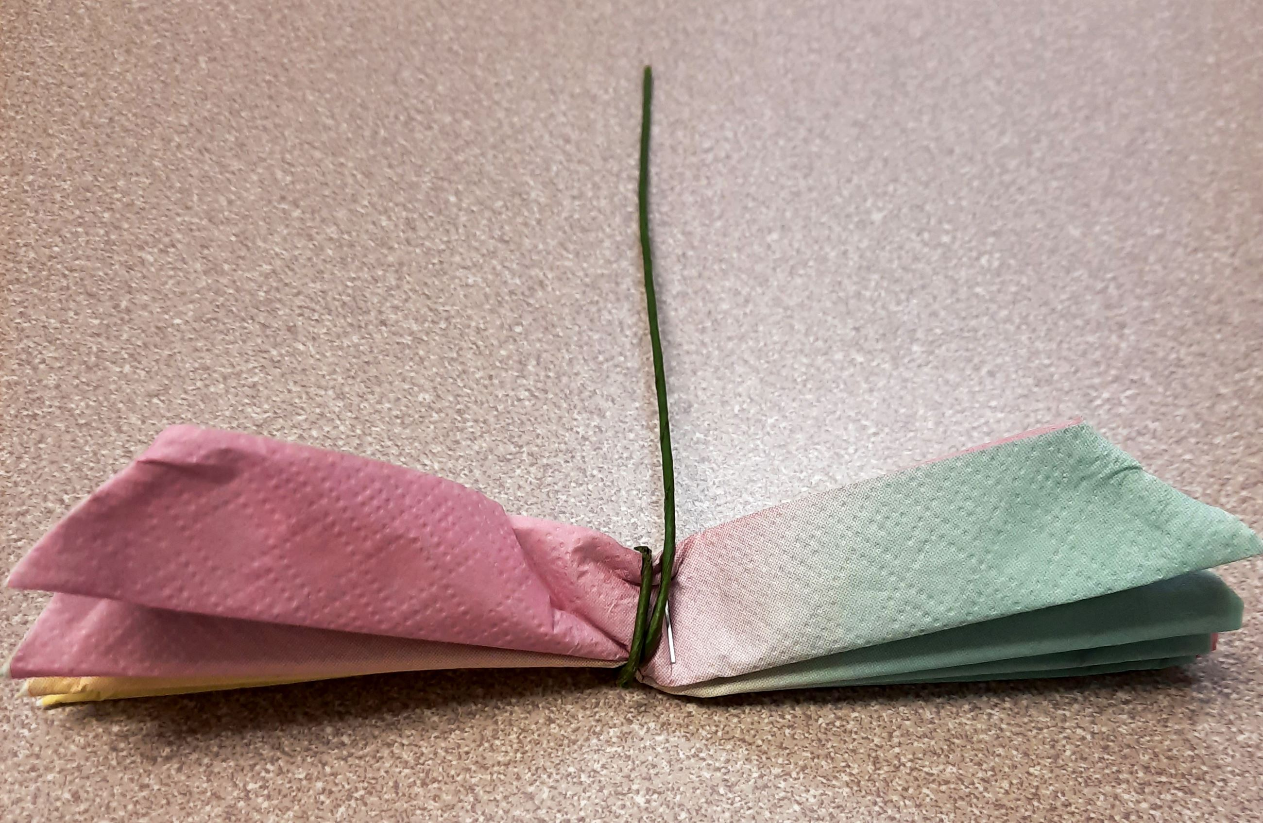Wrap the floral wire around the middle of the folded napkin.