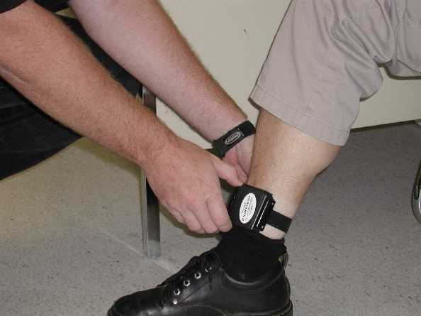 Someone putting an electronic tracker bracelet on someone else's ankle.
